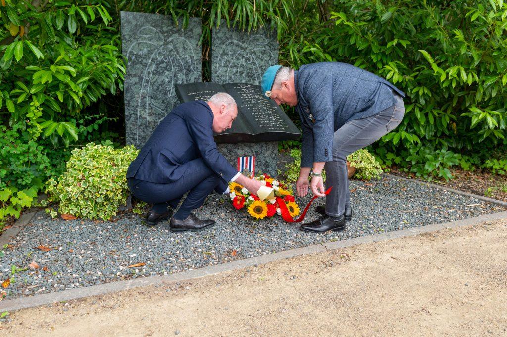 Twee mannen leggen een krans bij een monument