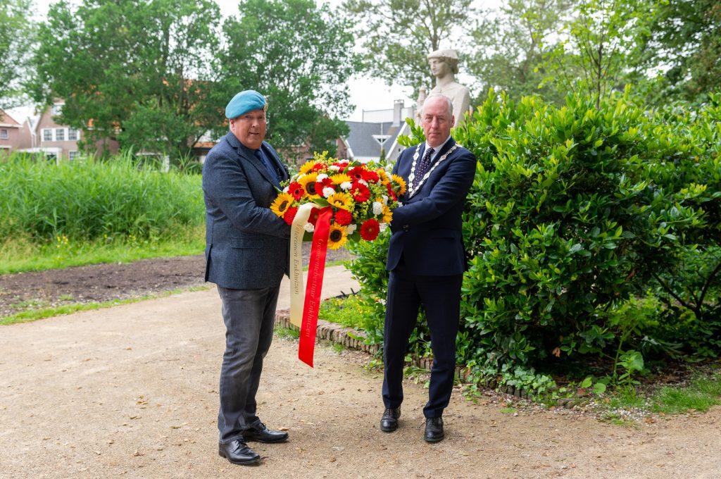 Twee mannen houden een bloemenkrans vast