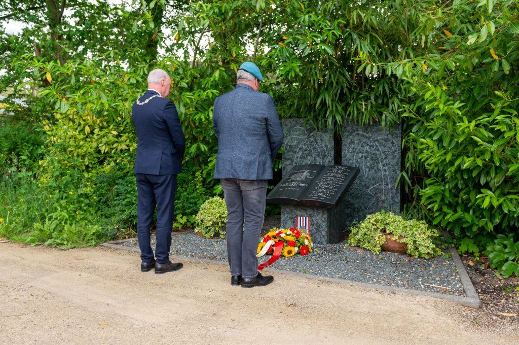 Twee mannen staan voor een monument